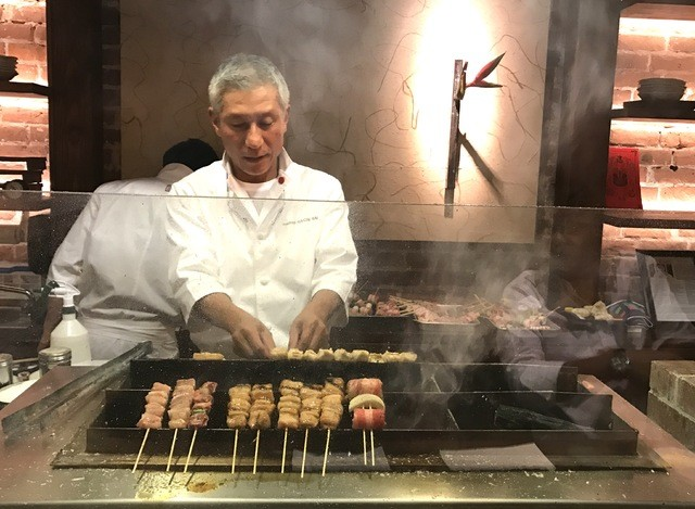 NADINE KAM / NKAM@STARADVERTISER.COM                                 Restaurateur Katsunori Yashima keeps a watchful eye on the charcoal grill at Yakitori Hachibei.